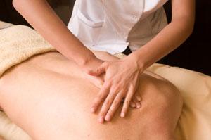 Sanfte Streichungen entlang der Wirbelsäule während einer Breuss-Massage